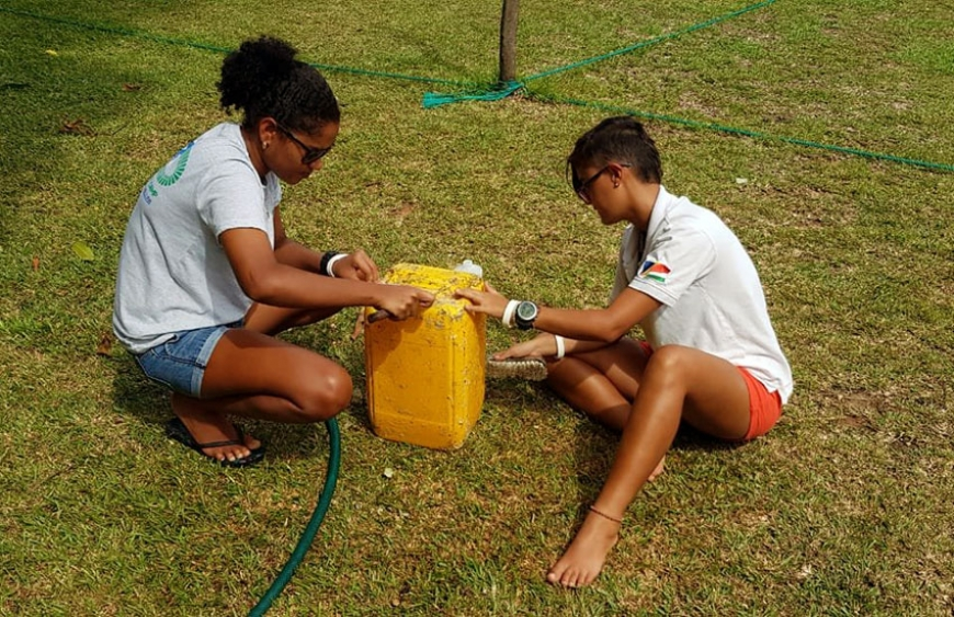 Camila and Athina carefully clean the old jerry cans